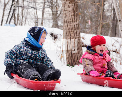 Brother and sisters (5 and 3 yrs old) sledging together in Quebec in winter - Stock Photo