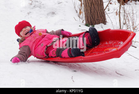A little girl (3 yr old) sledging in Quebec - Stock Photo