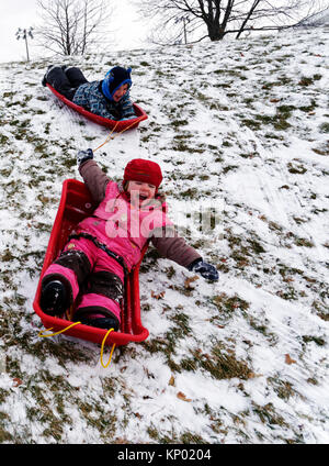 Brother and sister (5 and 3 yrs old) sledging together in Quebec City - Stock Photo