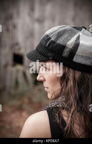 Young woman standing in front of an old barn. - Stock Photo