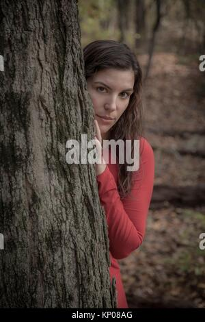 Young woman in a red dress standing behind a tree in the woods during autumn. - Stock Photo