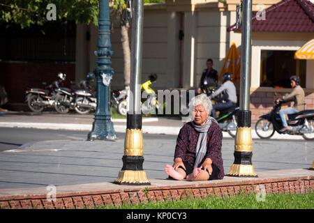 An elderly woman sitting by the roadside, Cambodia, Phnom Penh, Boulevard Sumararit, the Independence Monument in - Stock Photo