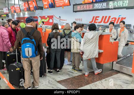 Family standing at airline check-in counter, Seoul, Korea - Stock Photo