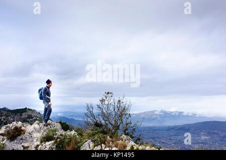 ountaineer on top of the mountain in Quatretondeta, Alicante, Valencia, Spain - Stock Photo