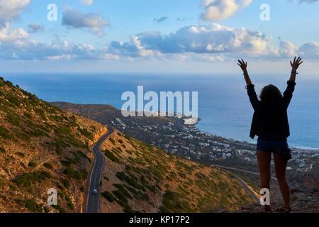 lively girl enjoying sunrise in mountains near Chersonissos, Crete, Greece - Stock Photo