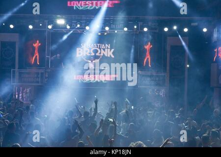 party crowd cheering at DJ Sebastian Bronk at music festival Starbeach Lovestar Neon in Hersonissos, Crete, Greece, - Stock Photo