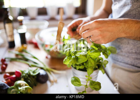 Unrecognizable young man cooking. - Stock Photo