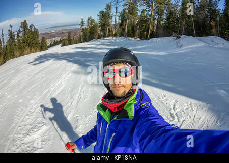 Man skier taking selfie photo with smart cell phone camera. - Stock Photo