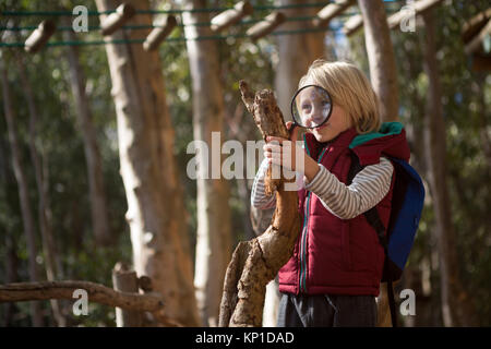 Little girl with backpack looking at wood through magnifying glass in the forest - Stock Photo