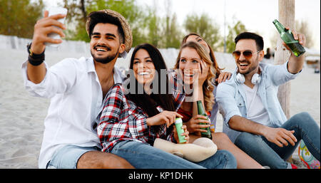Friends partying and having fun on beach at summer - Stock Photo