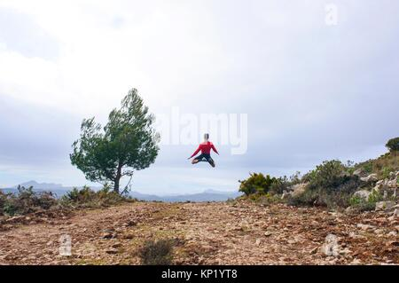 Sportsman jumping through the air in the mountains of Quatretondeta, Alicante, Valencia, Spain - Stock Photo