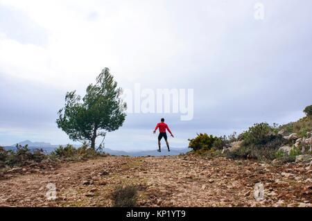Sportsman jumping through the air in the mountains of Quatretondeta, Alicante, Valencia, Spain - Stock Photo