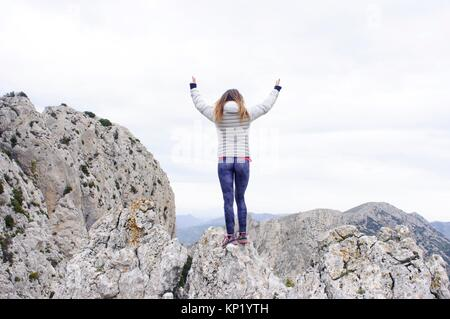 Woman on top of the mountain in Quatretondeta, Alicante, Valencia, Spain - Stock Photo