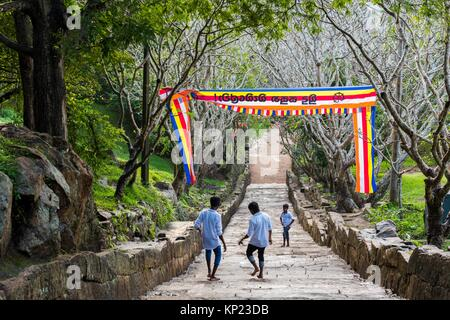 Three Young pilgrims Descending the Great Stairway of not less than 1,840 Steps to the top of Mihintale Mountain, - Stock Photo