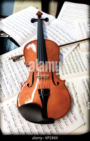 violin laying on sheets of music - Stock Photo