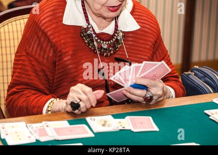 old woman playing canasta game - Stock Photo