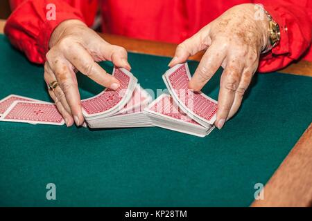 old woman shuffling canasta game cards - Stock Photo