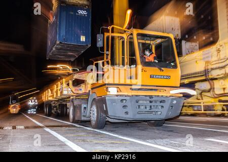 Stationary yellow cargo truck being loaded with a blue container of goods in Santa Cruz de Tenerife dock at night - Stock Photo