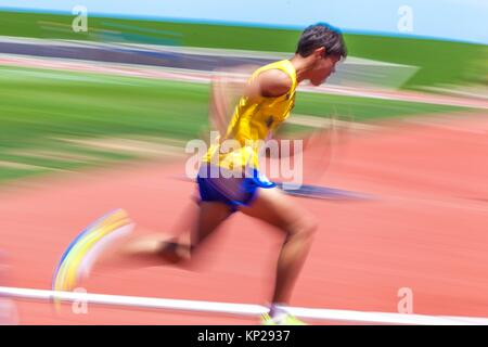 young man doing Hurdling on the track and field stadium CIAT in Santa Cruz de Tenerife city during the 22nd april - Stock Photo