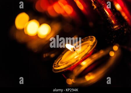 Lit candle set inside a San Cristobal de La Laguna cathedral - Stock Photo