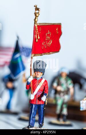 Tiny miniature vintage Grenadier Guard figurine holding a british flag standing - Stock Photo