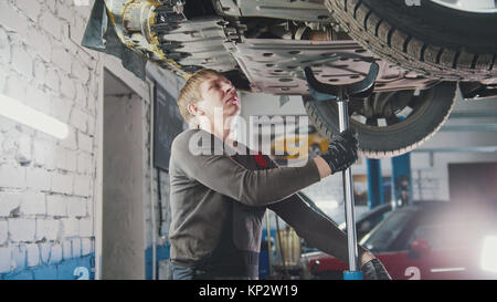Mechanic unscrewing parts of automobile's bottom under lifted car - Stock Photo