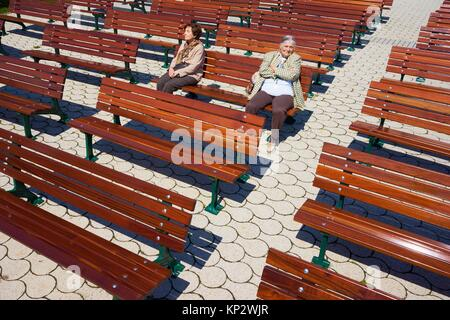 two lonely old senior women sitting between empty benches and ignoring each other - Stock Photo