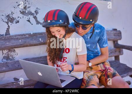Young couple using mobile laptop during break at road trip