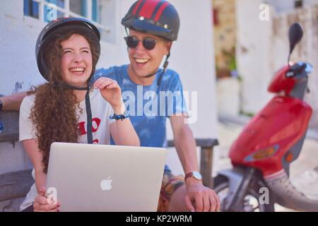 break at road trip with scooter: happy young English woman using mobile laptop while sitting next to attractive - Stock Photo