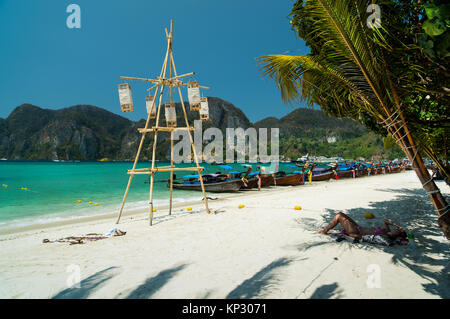 Tonsai Beach bay view with many traditional longtail boats parking and palm seafront in Thailand, Phi Phi island, - Stock Photo