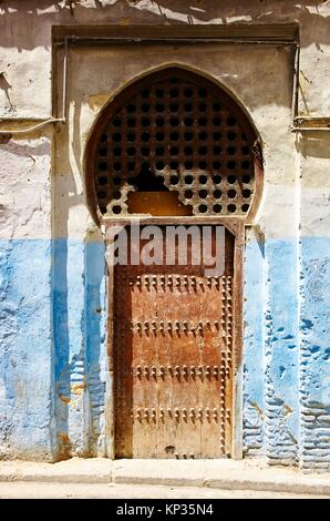 An old door and the blue painted walls of the narrow alleys in the medina of Fez, Morocco - Stock Photo