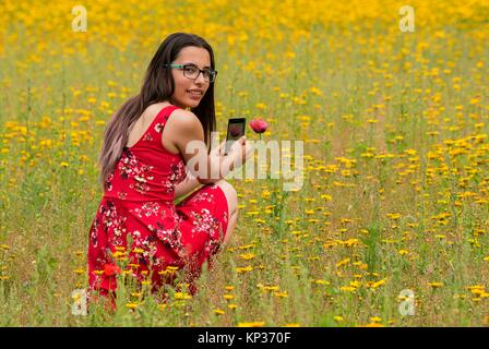 Girl with a red dress taking a photograph to a flower with a mobile in a yellow field. - Stock Photo