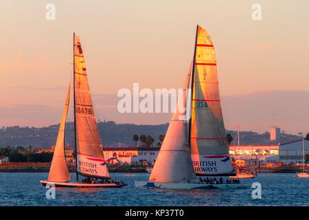 Two sailboats cruise San Diego Bay close to sunset in Southern California - Stock Photo