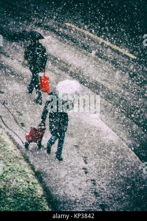 two persons passing each other on the street in heavy snowfall, winter in Geneva, Switzerland, Europe - Stock Photo