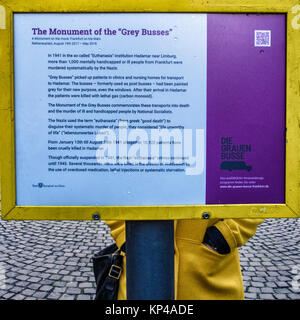Frankfurt,Germany.Young woman in yellow coat reads Grey Buses Monument information board. Memorial commemorates - Stock Photo