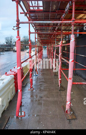Safe passage for pedestrians made out of red scaffolding on a typical construction site in UK. - Stock Photo