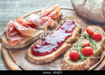 Bruschetta with different toppings on the wooden board - Stock Photo