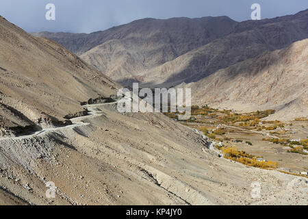 the curvy road leading to the pass Changla with villages in the valley below, Ladakh, Jammu and Kashmir. India. - Stock Photo