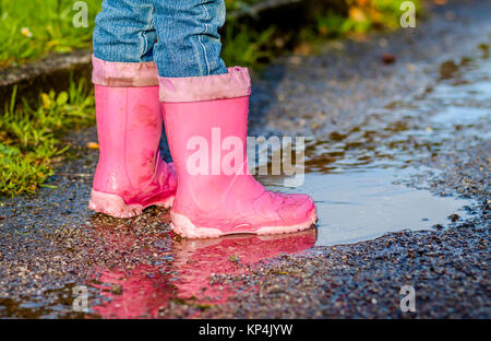 Little girl with pink wellys in the puddle on the street - Stock Photo