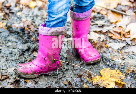 Little girl with pink wellys in the puddle on the forest - Stock Photo