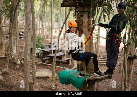 Happy woman leaning on zip line while man standing on wooden platform holding rope in the forest - Stock Photo