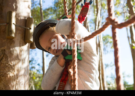 Little girl wearing helmet standing on rope fence in the forest - Stock Photo