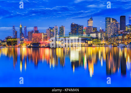 Bright iilluminated waterfront urban architecture of Docklands suburbs in Melbourne reflecting in still waters of - Stock Photo