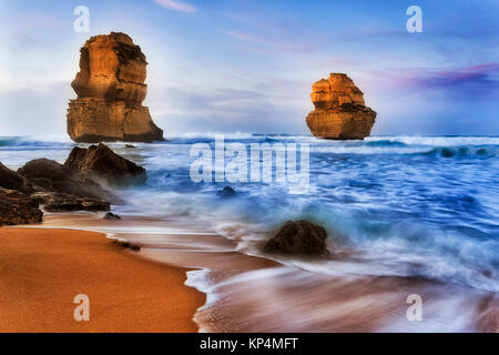 two apostless off Gibson Steps beach at sunrise in surfing waves breaking limestone cliffs and rocks - part of famous - Stock Photo