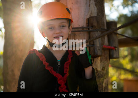 Close-up of portrait of beautiful little girl wearing helmet in the forest - Stock Photo
