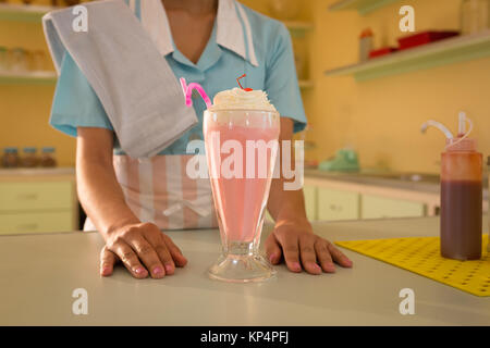 Mid section of waitress with ice cream on table in restaurant - Stock Photo