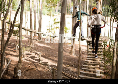 Couple walking on wooden obstacle bridge in the forest on a sunny day - Stock Photo
