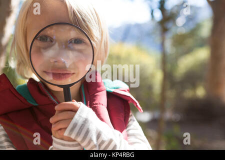 Close-up of little girl looking through magnifying glass in the forest - Stock Photo