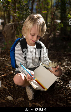 Close-up of little girl with backpack sitting on ground writing in notebook - Stock Photo