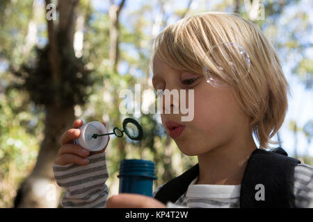 Close-up of little girl blowing bubbles on a sunny day in the forest - Stock Photo
